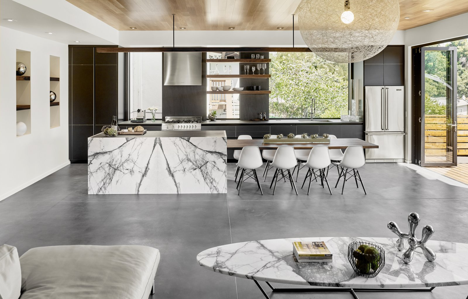 Kitchen, Range Hood, Marble Counter, and Pendant Lighting The floors have hydronic heating embedded in a matte finished concrete. The stone slab is Calacatta Viola. The table is custom designed by the architect and fabricated by Gerardo Villa.  Trestle Glen Modern by Knock Architecture + Design
