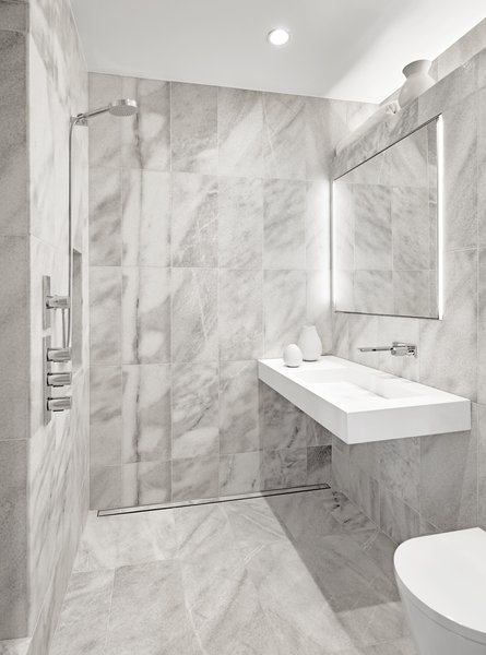The private bathroom features a wetroom style open enclsoure, linear drain,Quartzite tile, and a concealed mirrored medicine cabinet. The fixtures are by Fantini.