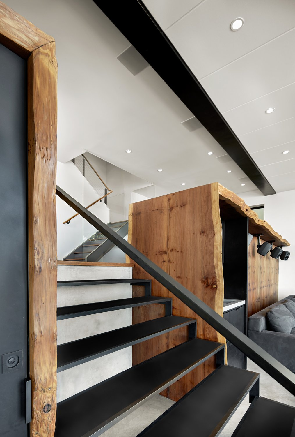 Staircase, Metal Tread, and Metal Railing The custom steel stair by Metropolis Metalworks serves as the centerpiece to the space. The live edge burled Redwoods slabs covers the listening area and wetbar. In the distance, the stair leads up to the rest of the home and more everyday life.  Photo 3 of 6 in Top 5 Homes of the Week With Top-Notch Woodwork from Twin Peaks Escape Pad