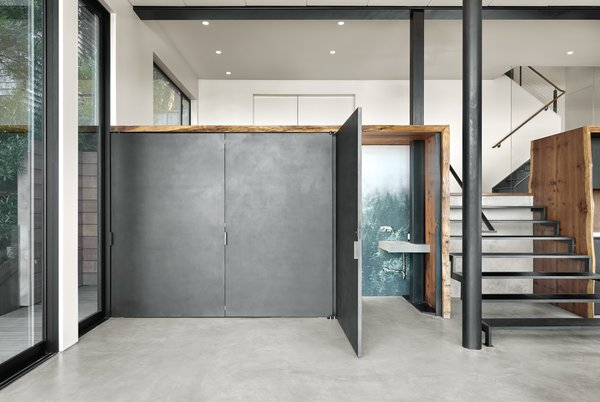 """The other side of the """"vault"""" houses a powder room with a concealed toilet and nature inspired wallpaper. The single slope sink is a custom piece by Concrete Interiors who also fabricated the wetbar countertop. The wall mount faucet is Axor by Hansgrohe."""