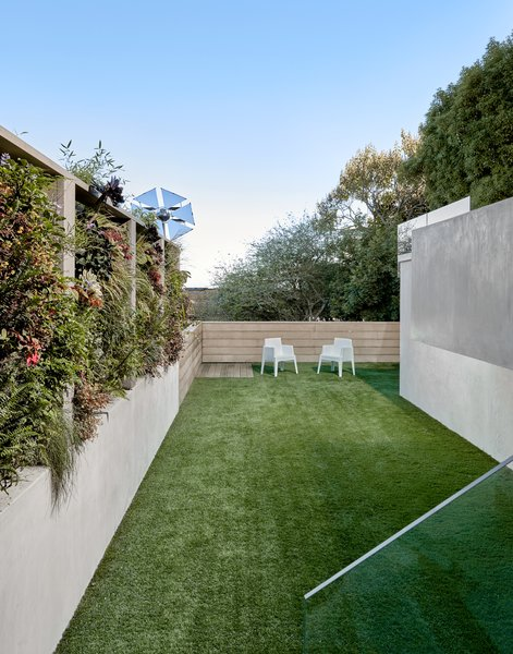 The yard is at the lowest elevation on the property, and was carved out to have a place for the family to play and relax. The turf is by Heavenly Greens. The space features clear heart cedar boards with a reactive stain by Weatherwood Stains.  The 30 foot green wall in implemented in segments and features built in drip irrigation. The mirrored solar reflector, which appears to have just dropped out of planetary orbit,  grabs southern light and reflects it into the home and exterior spaces.