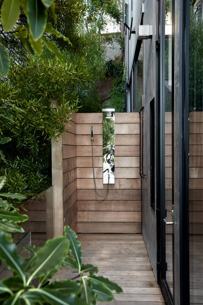 An outdoor shower is concealed in the side yard and features a weathered  cedar slat enclosure.