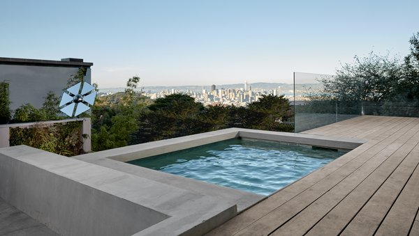 The custom built spa was a must have for the homeowners, and features a concealed solar cover beneath the deck boards. It was raised to offer the dramatic view of downtown San Francisco and the East Bay Hills beyond. The interior of the spa is integral color plaster with a Quartzite slab liner at the water line. The sunken conversation pit lies next to the spa and features radiant tubes imbedded in its cantilevered concrete seat.