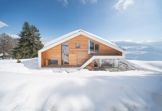 Inspired by traditional chalets of the Swiss Alps, Dutch architects SeARCH designed this 500-square-meter home as a single, visually clear volume with wood cladding and decidedly modern glazing and windows.