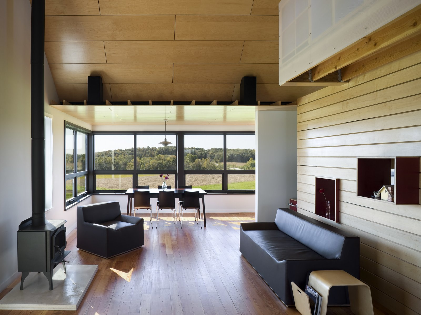 Living Room, Wood Burning Fireplace, Chair, Sofa, and Medium Hardwood Floor Yum Yum Farm in Iowa  Photo 6 of 11 in Dwell's Top 10 Design Pros of 2017 from Yum Yum Farm