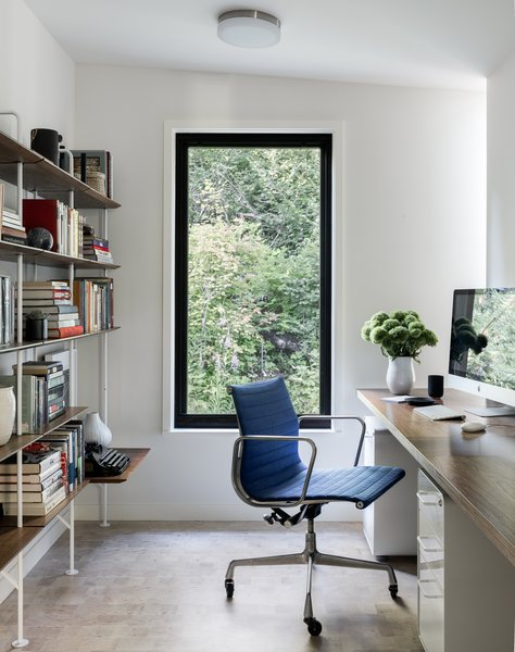 The home office in Tree House by Deforest Architects offers a striking view of the surrounding trees.