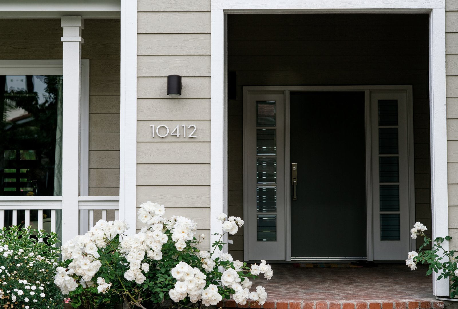 Outdoor, Front Yard, Hardscapes, Flowers, Walkways, Shrubs, and Large Patio, Porch, Deck Contemporary lighting and signage details at the traditional front entry hint at the modern interior.  Villa Park Modern by MYD studio, inc.