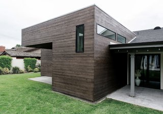 The contemporary addition features dark cedar siding and a flat roof at the existing gable structure and rear patio.