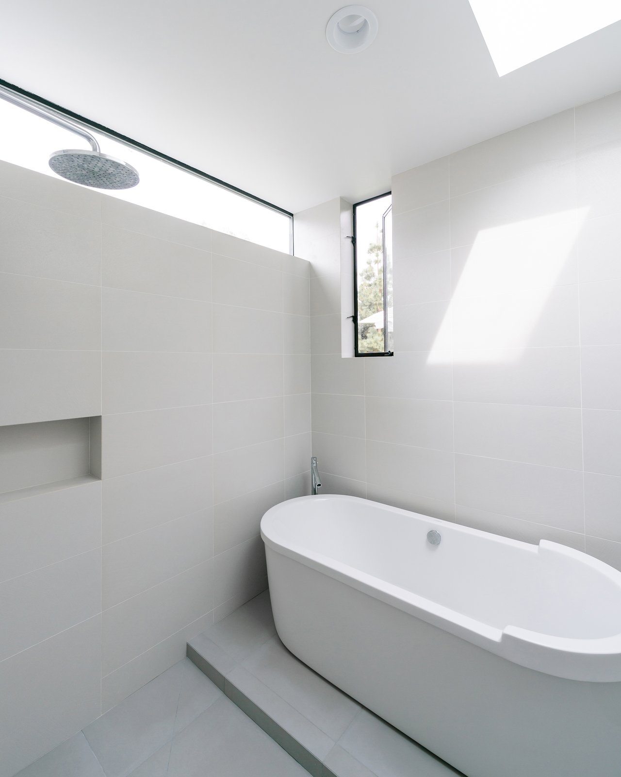 Bath Room, Porcelain Tile Floor, Recessed Lighting, Freestanding Tub, Porcelain Tile Wall, Ceiling Lighting, and Open Shower At the rear of the home, the master suite addition adds a full wet room with skylight, a rain shower and freestanding tub.  Villa Park Modern by MYD studio, inc.