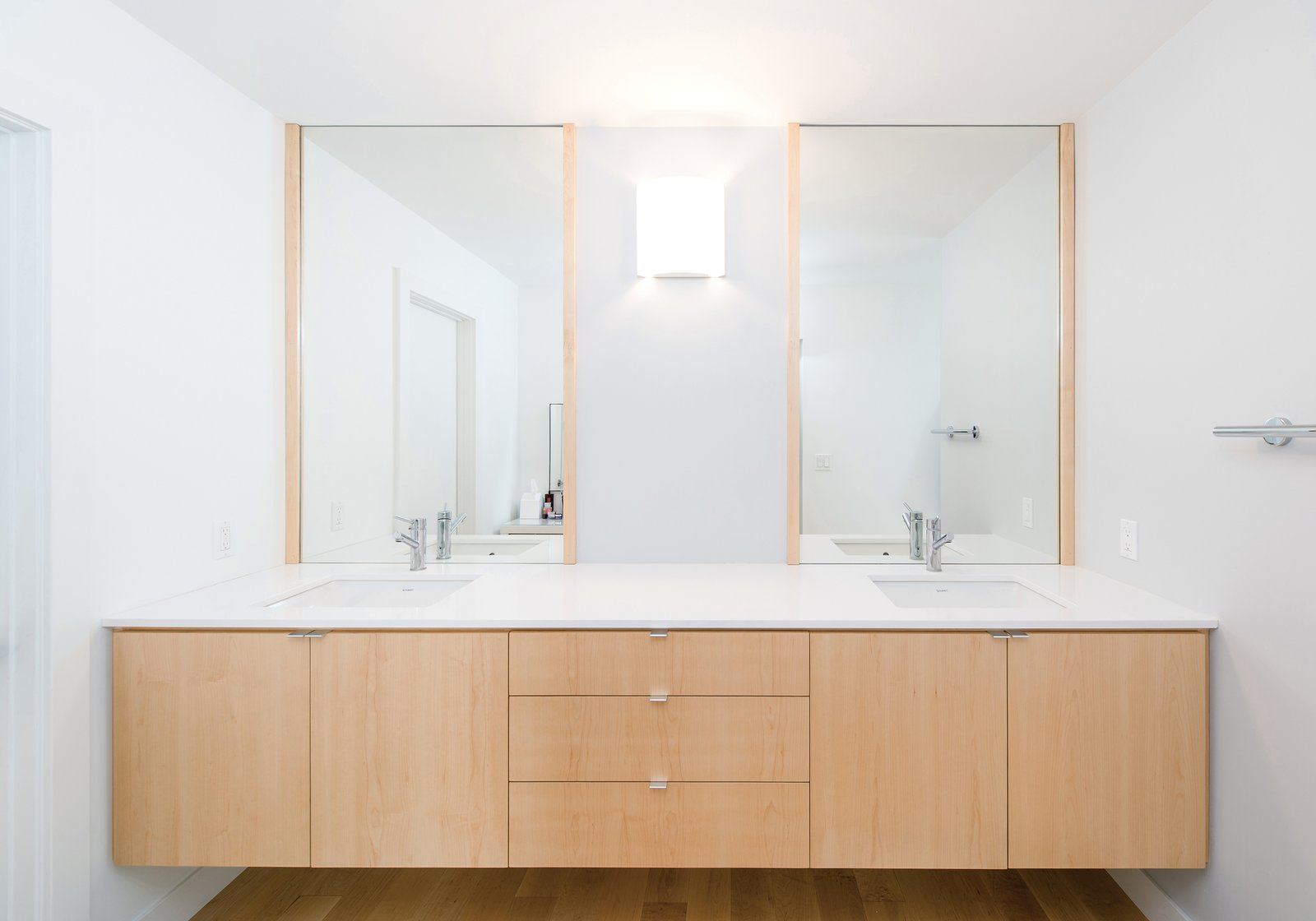 Bath Room, Engineered Quartz Counter, Wall Lighting, Undermount Sink, and Light Hardwood Floor Floating maple cabinetry at the master bath vanity provides for material continuity throughout the home's minimalist interior.  Villa Park Modern by MYD studio, inc.