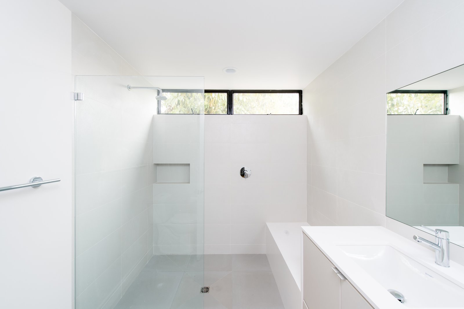 Bath Room, Engineered Quartz Counter, Porcelain Tile Floor, Undermount Sink, Open Shower, Ceiling Lighting, and Ceramic Tile Wall A minimalist secondary bath features a quartz waterfall bench and oversized custom shower.  Villa Park Modern by MYD studio, inc.
