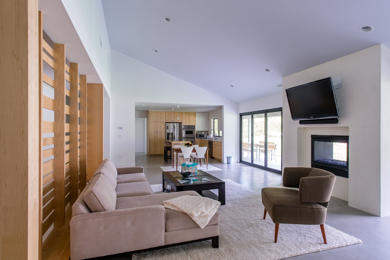 Living Room, Chair, Sofa, Table, Ceiling Lighting, Concrete Floor, and Two-Sided Fireplace The open floor plan features a bi-folding door system and dual-sided fireplace to provide a strong connection to the rear landscape and views.  Villa Park Modern by MYD studio, inc.