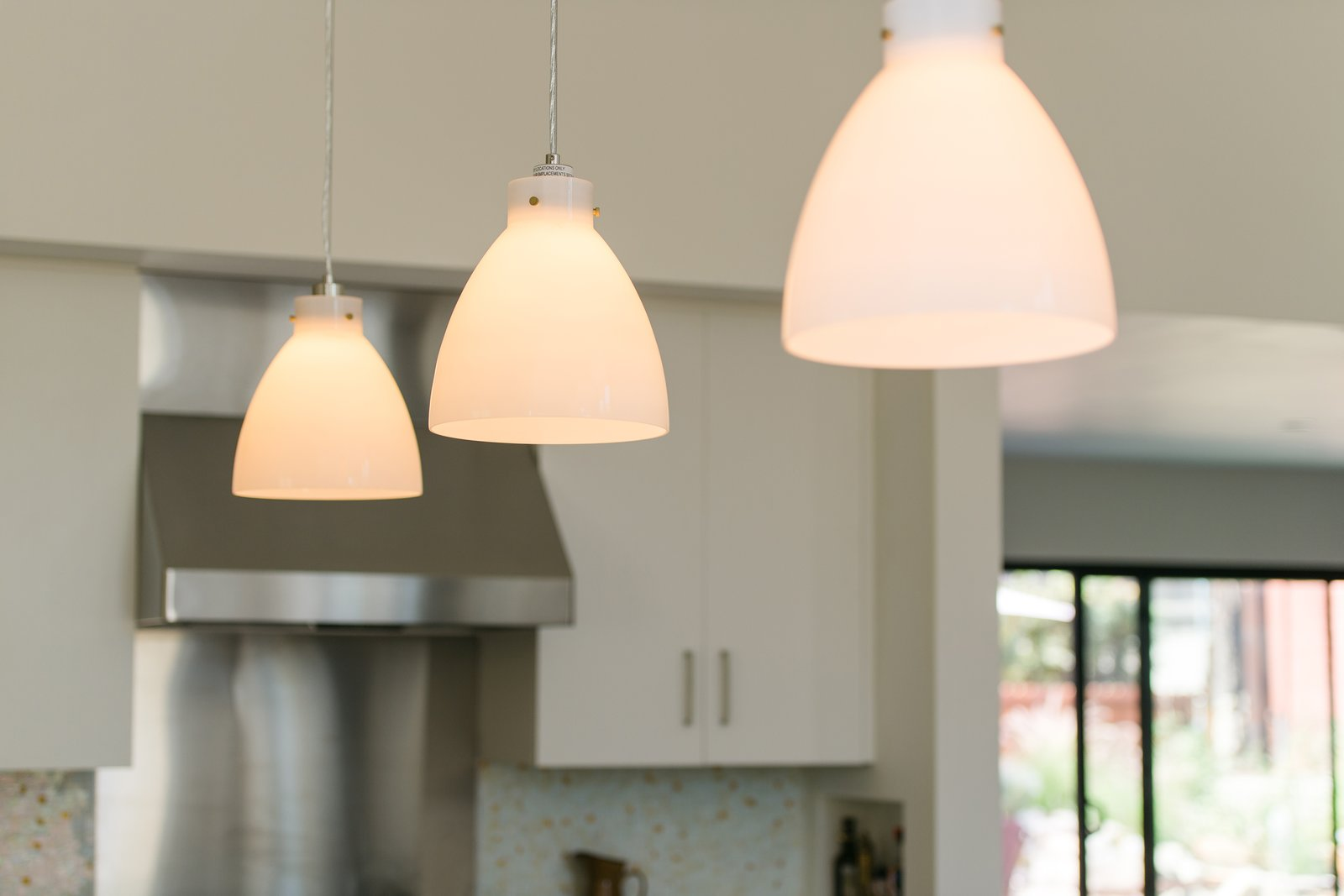 Minimal pendants add warm, intimate lighting at the oversized kitchen island.  A California Ranch Home, Reimagined by MYD studio, inc.