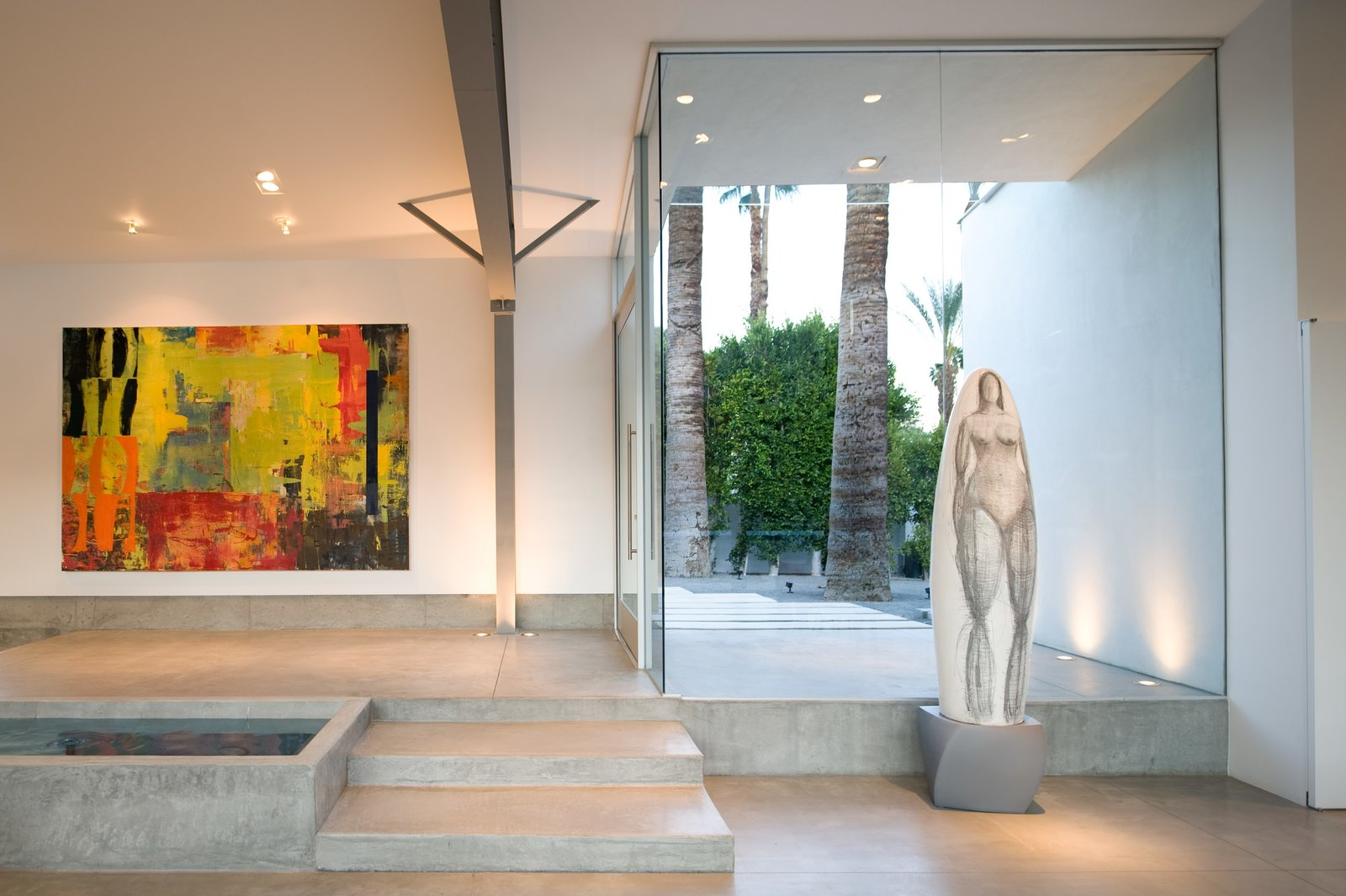 Living Room, Ceiling Lighting, Floor Lighting, and Concrete Floor The front entrance opens into the great room next to a linear pond. The home becomes a perfect showcase for the owner's artwork collection.   Desert Canopy House