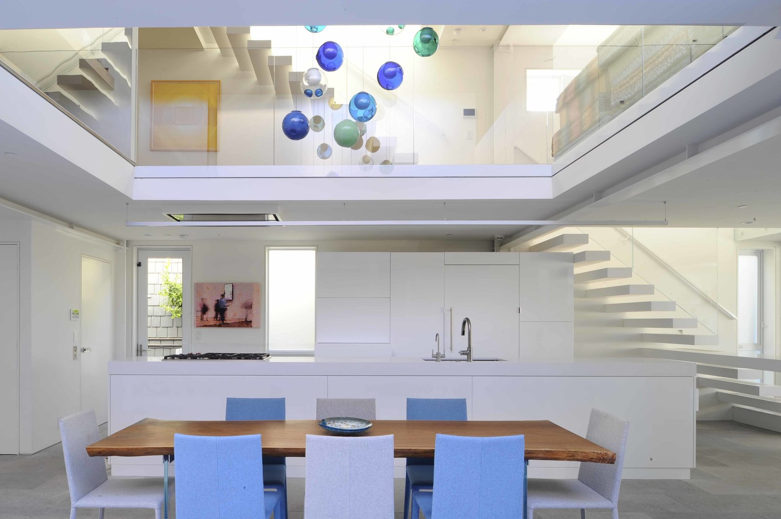 Kitchen, Pendant, White, Limestone, Quartzite, Ceiling, Refrigerator, Microwave, Dishwasher, Wine Cooler, Range, Range Hood, and Undermount The all-white kitchen is open to the upper level. One tread of the stairs extends out to become a countertop and the live-edge dining room table is surrounded by blue and grey chairs that are part of a palette inspired by the beach setting.  Best Kitchen Microwave Range Hood Limestone Ceiling Dishwasher Refrigerator Photos from Beach House