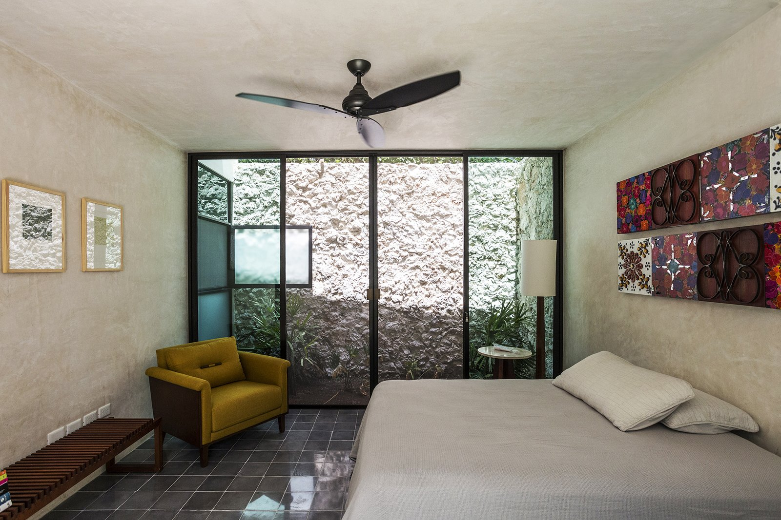Bedroom, Chair, Cement Tile Floor, Lamps, and Bed A Light well provide natural light and ventilation to the downstairs bedroom  Lemon Tree House by Taller Estilo Arquitectura S de R.L de C.V