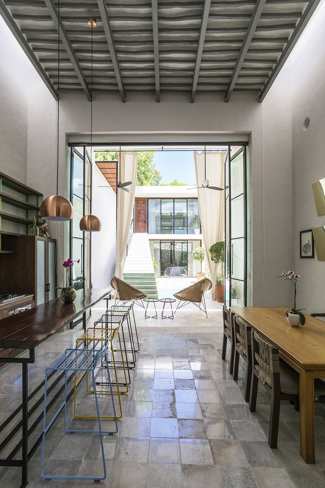 The transistion from Outside-Inside- is gradual, same concept to the transition from the old struture to the contemporary  architecture. Tagged: Dining Room, Pendant Lighting, Table, Chair, and Bench.  Lemon Tree House by Taller Estilo Arquitectura S de R.L de C.V