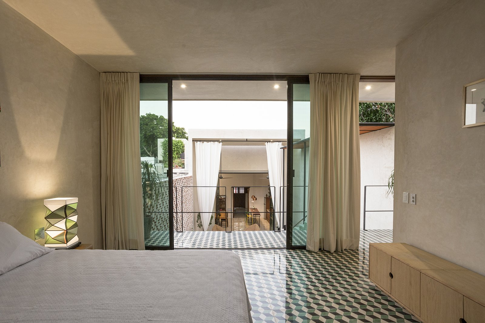 Bedroom, Bench, Table Lighting, Bed, Cement Tile Floor, and Bookcase A great view from the upstairs bedroom  Lemon Tree House by Taller Estilo Arquitectura S de R.L de C.V
