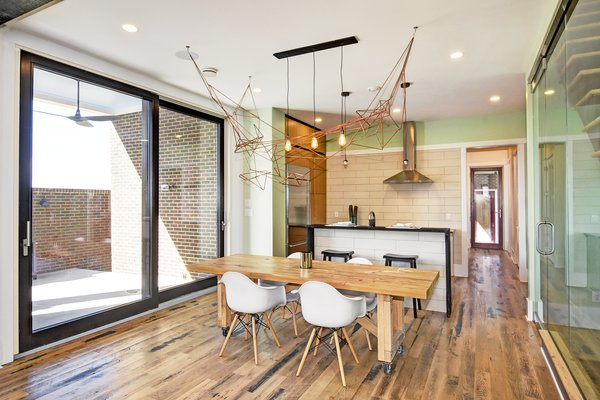 The bright and airy open floor plan features hardwood floors that are made from reclaimed wood from Kentucky horse farm fences. Shown is a reclaimed wood dining room table by Rework Collective and a biophilic chandelier from Honest Home by local Artist Leah Naomi.