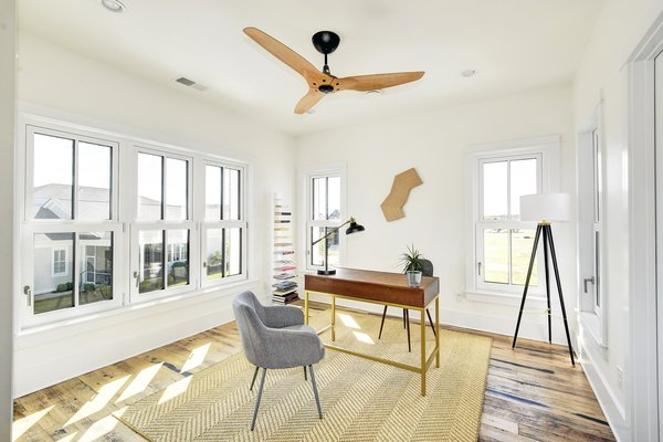 One of the bright and airy bedrooms, currently used as an office space, features a Haiku Home ceiling fan.