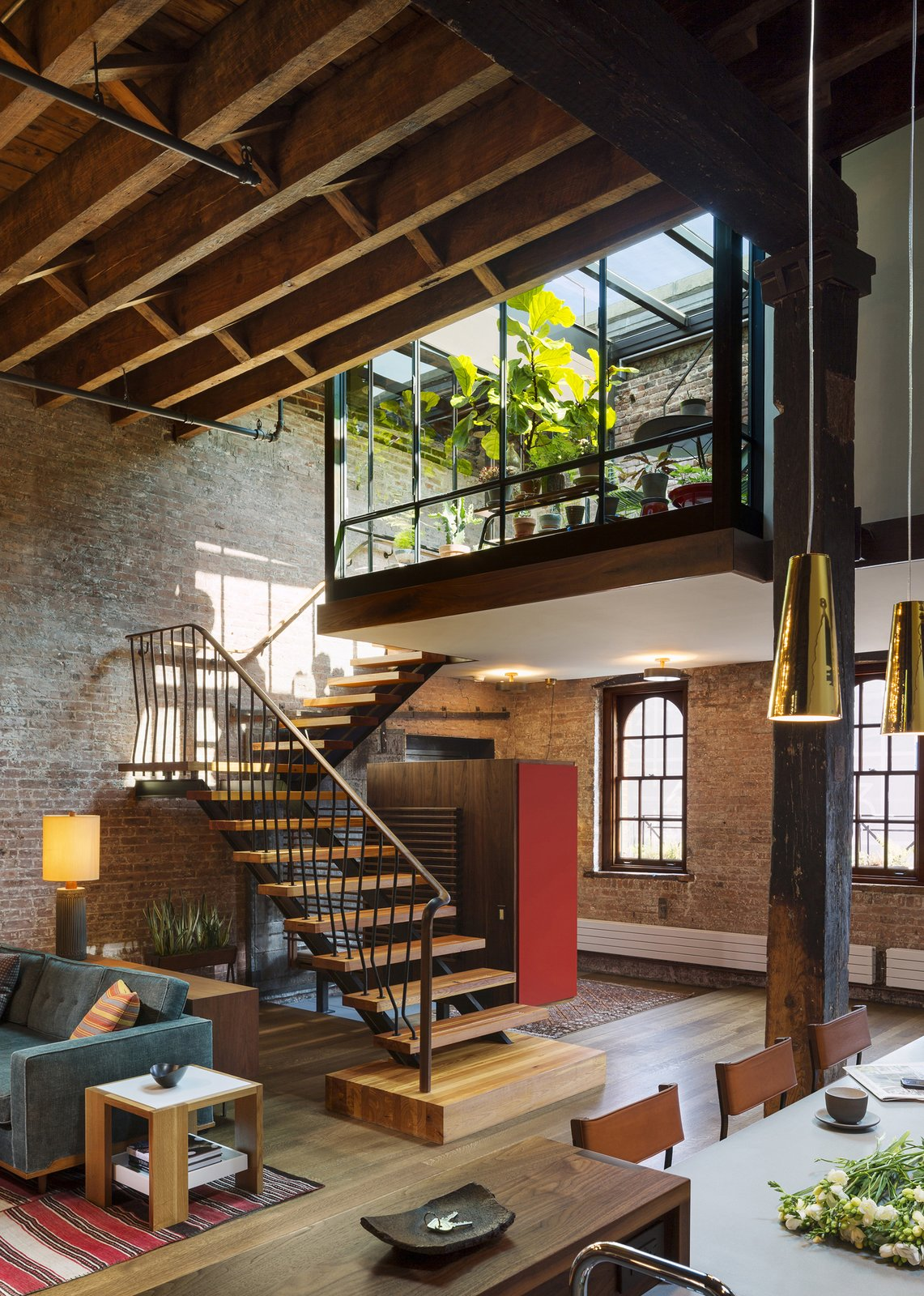 A custom steel stair repurposes timbers from the old roof joists as treads and landings.  Tribeca Loft by Andrew Franz Architect PLLC