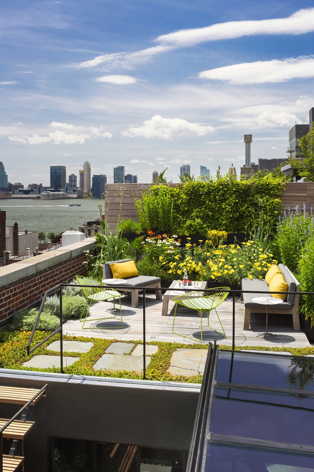 The new wooden rooftop terrace is surrounded by a green roof garden utilizing reclaimed bluestone pavers and native plant species that require little water while insulating the environment below.  Tribeca Loft by Andrew Franz Architect, PLLC