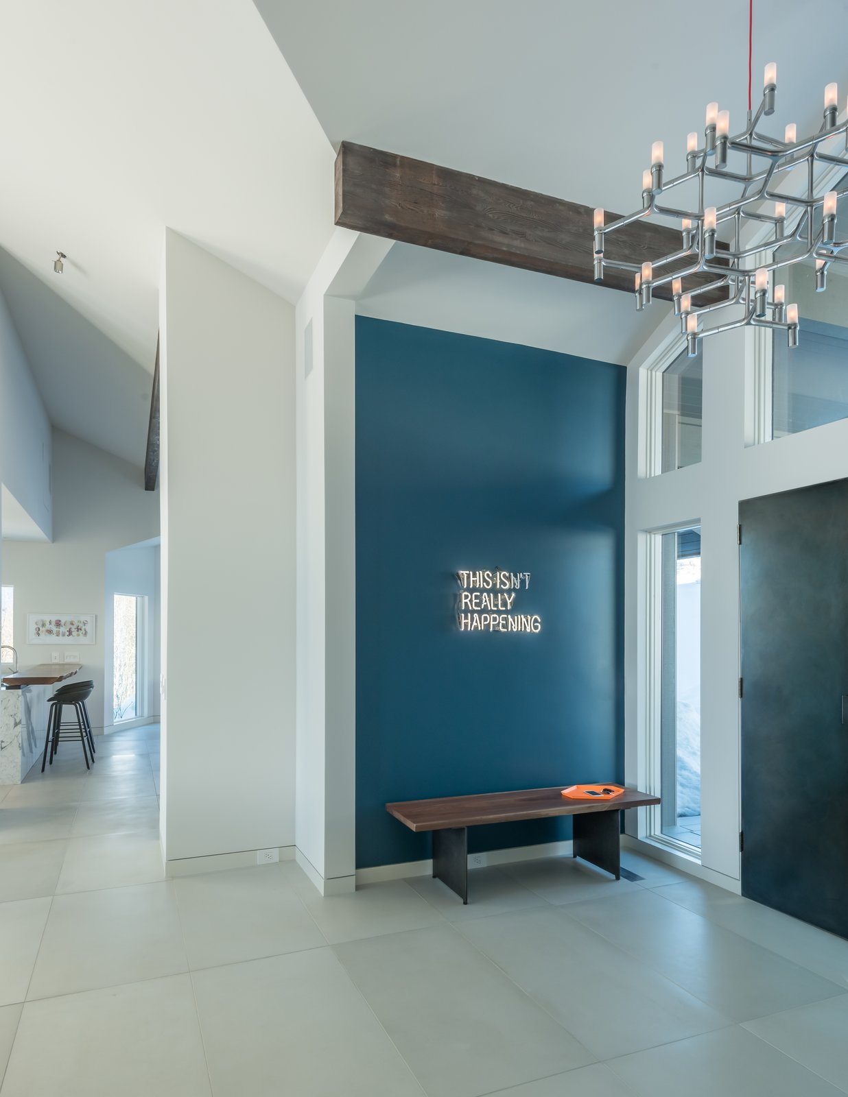 A playful neon wall installation greets guests.  Crown Major Suspension pendant and entry doors clad in steel set the tone for the interior spaces.  San Francisco Meets Jackson Hole in a Modern Renovation