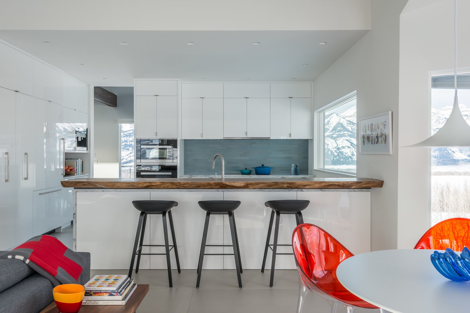 Kitchen cabinets are painted white and lacquered with an automotive finish.  Heath Tile adds color in the backsplash while a live-edge walnut counter adds depth to the room.  San Francisco Meets Jackson Hole in a Modern Renovation