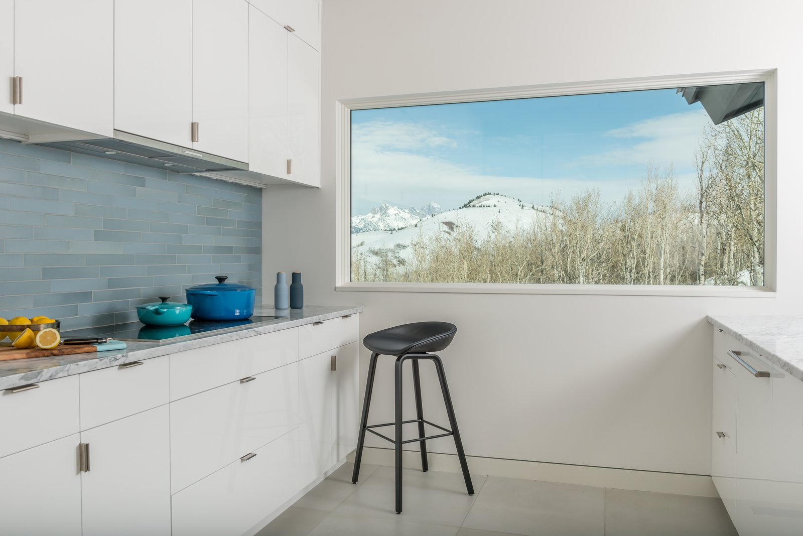 Honed, white Carrera marble countertops blend with exterior views to the Teton Mountain Range.  San Francisco Meets Jackson Hole in a Modern Renovation
