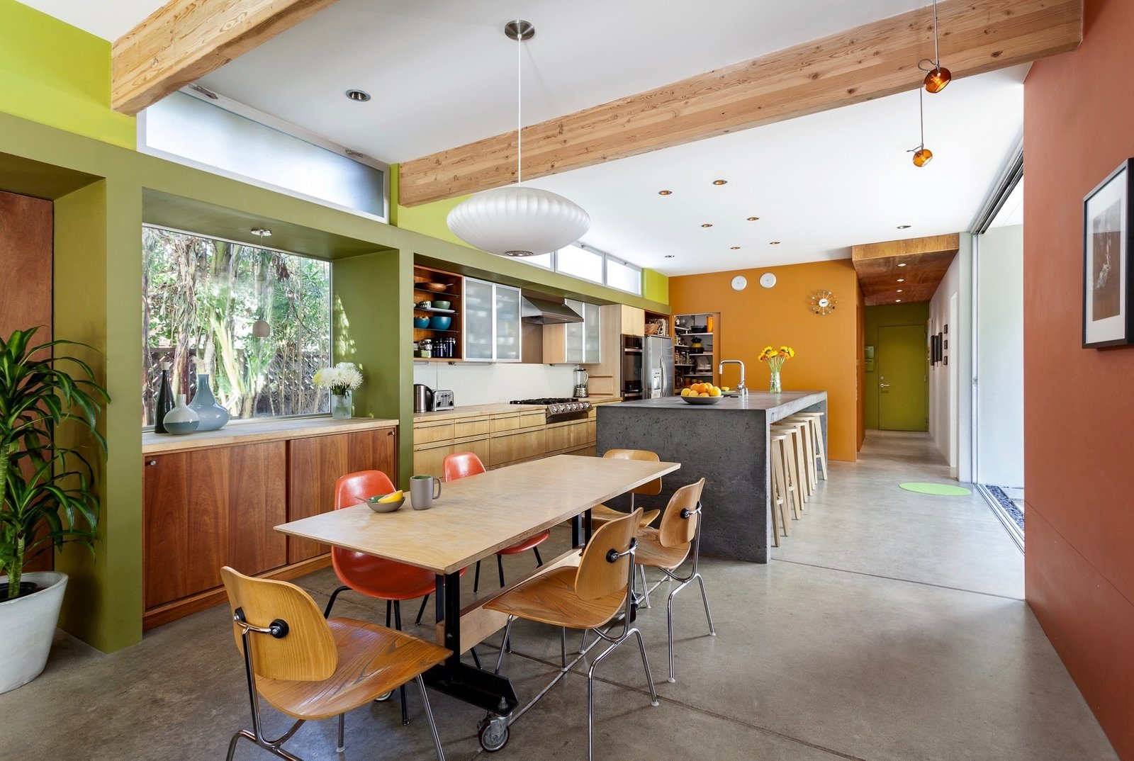 Concrete Counter, Dining Room, Table, Bar, Stools, Accent Lighting, Chair, Storage, Pendant Lighting, Recessed Lighting, and Concrete Floor Dining Room to Kitchen  Land Park Residence by serrao design | Architecture