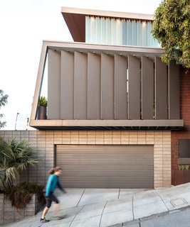 Steep street. Original garage door and wooden louvers.  New third floor glass louvers.