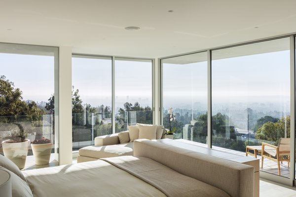 A singular recessed light nestled in the white ceiling is all that's needed in this expansive room with 270 degrees of floor-to-ceiling windows.