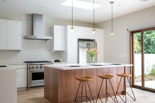 Open Kitchen blends modern and organic finishes for functionality and warmth. New skylight above floods the space with daylight. Appliances: Monogram by GE; Cabinet Finishes: Matte Lacquer and Natural Walnut by Semi-Handmade; Countertops: Statuario Nuvo by Caesarstone; Backsplash: Made by Ann Sacks.