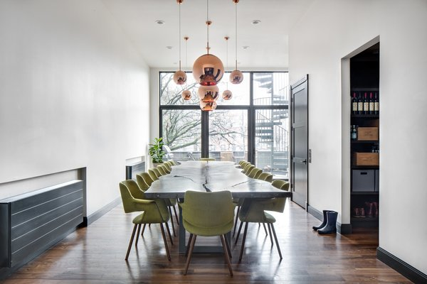 On the second floor they created one large continuous space complete with multiple seating areas, a large kitchen, and a dining room that accommodates 14, as the homeowners routinely host neighborhood dinners on Sundays.