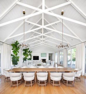 """When in doubt, go with white"" was a guiding design principle on this project by interior designer Eric Ford.Exposed wooden white beams create unique patterns in the open concept living and dining room, floating high above the table for twelve."