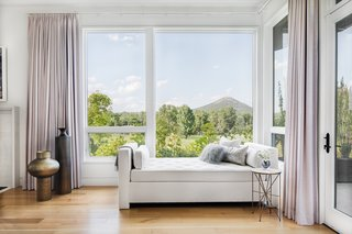 A beautiful daybed in the master bedroom boasts a second story view of the expansive five acres of land and Mount Pinnacle.