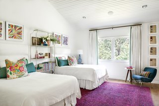 Two of the girls share a bedroom that keeps the theme of light and bright, with pops of fun colors in the rug and accessories.