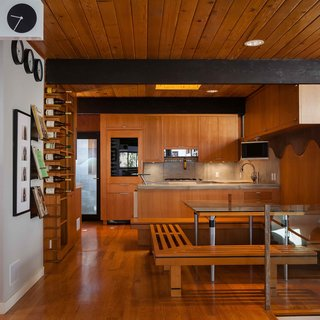 Dining area and Kitchen. Built in seating for both dining and wine rack and poured in place concrete counters/backsplash. Custom alder cabinets designed to wrap around the beams.