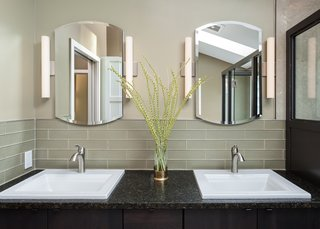 Dual, white square-shaped sinks make the perfect modern bathroom vanities for granite countertops, like the contrasting black one seen here.