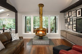 The original circular brass Malm fireplace sits atop its new tiled platform in the opened up living room. Since the home's setting feels very park-like, the new covered deck—visible just outside the windows—was designed to add year-round living space to the home.