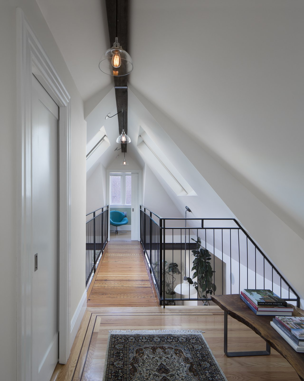 Hallway and Light Hardwood Floor former attic space now living space, view across bridge  Bridge House by McElroy Architecture