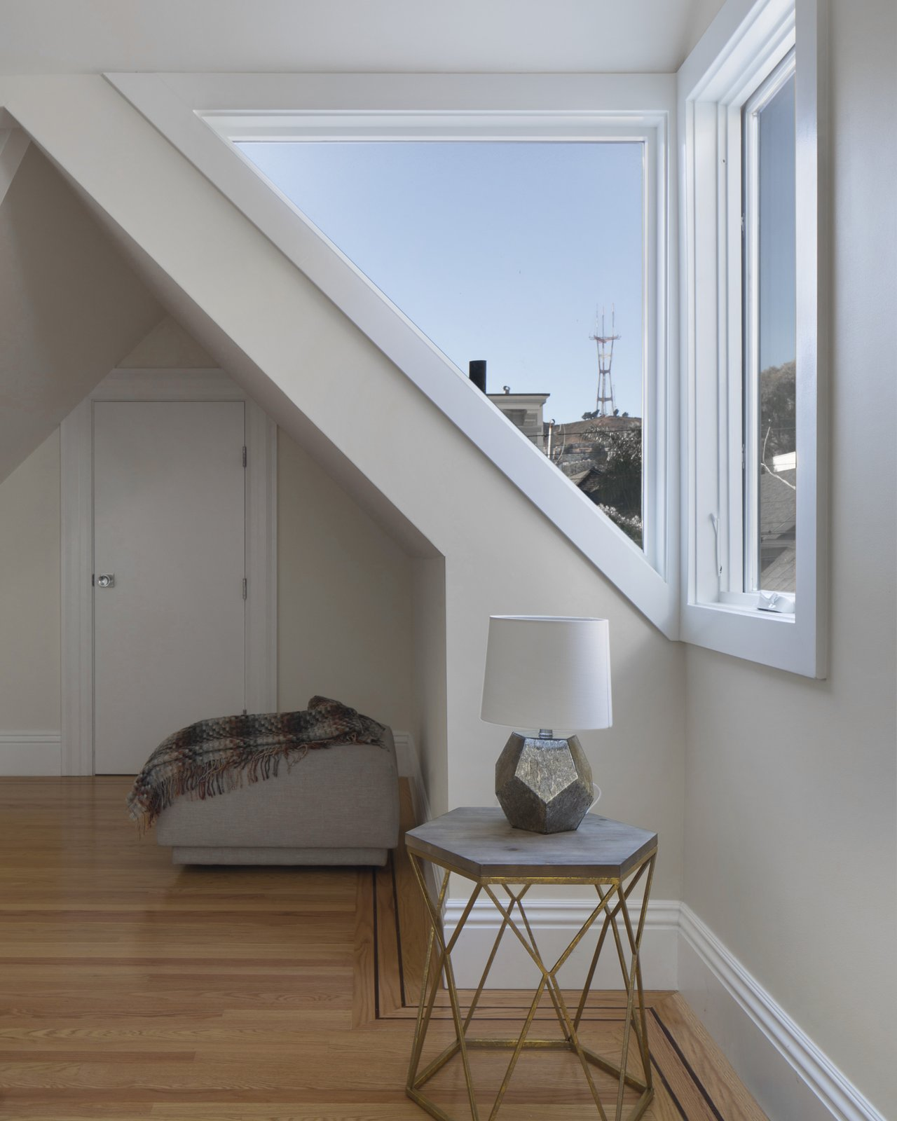 Bedroom, Light Hardwood Floor, and Bench angled window in new dormer with view of Sutro Tower at Twin Peaks  Bridge House by McElroy Architecture