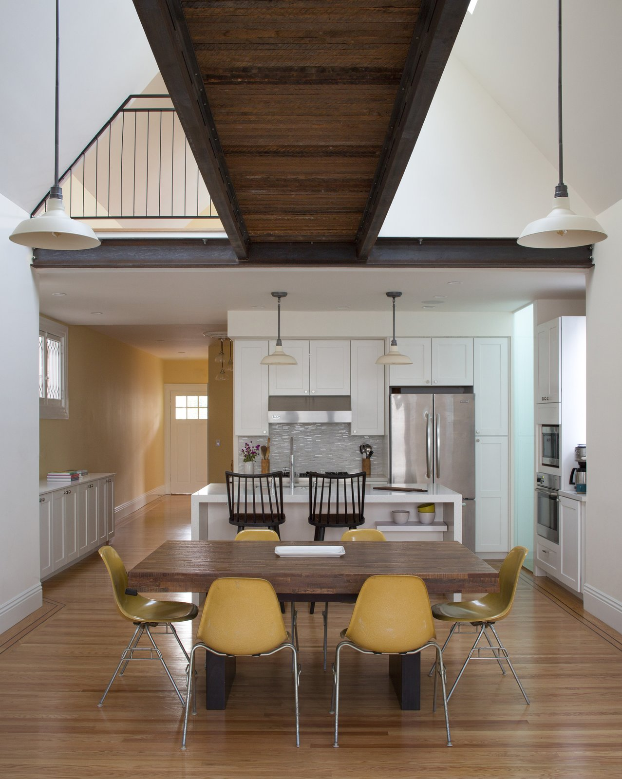 Dining Room, Light Hardwood Floor, Pendant Lighting, and Chair view of dining and kitchen with bridge above  Bridge House by McElroy Architecture