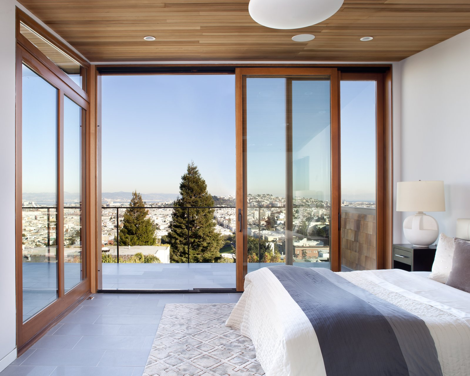 Bedroom, Night Stands, Bed, Porcelain Tile Floor, Recessed Lighting, and Pendant Lighting cedar wood ceiling quantum sliding doors porcelain tile flooring master bedroom  Bungalow Update by McElroy Architecture