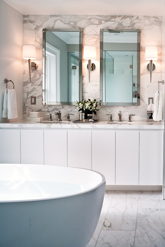This slick bathroom by Powell & Bonnell features a trio of Pacific Heights Sconces designed by Barbara Barry for Boyd Lighting. With its vertically faceted form, the Pacific Heights wall sconce is a classic workhorse fixture for residential bedrooms, bathrooms, living rooms, dining rooms, libraries and offices. Aggressively priced for commercial and hospitality spaces. Available in three metal finish options. Photo by Ted Yarwood. #lighting #bathroomlighting #bathroom #sconce #bathroomsconce #shadedsconce #lightingdesign #classiclighting  Boyd Lighting Freshens Up Bathrooms