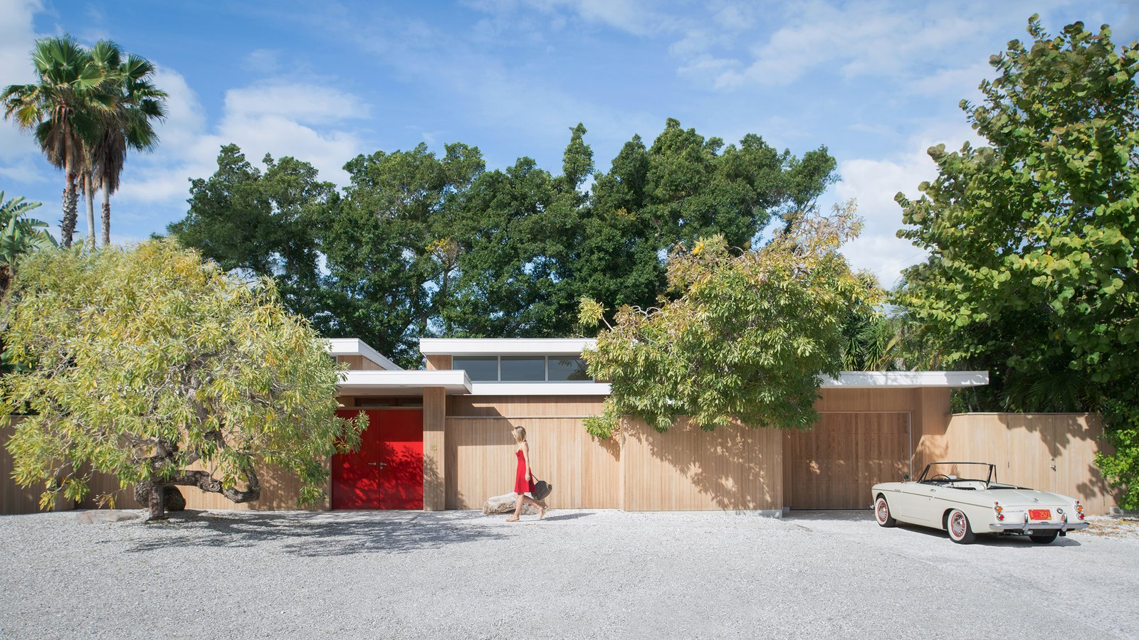 The Pavilion House's outer wall encircles a snaking courtyard that connects many of the home's interior spaces. After a step inside the lipstick red door, guests are greeted with an entrance into the home's exterior or to private patio on the left. Within that outer wall, both indoor and outdoor spaces appear to be one in the same.  The Pavilion House by Seamus Payne