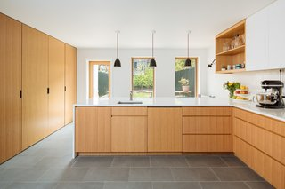Custom-made white oak cabinetry provides a sleek contemporary look and minimalist interiors.