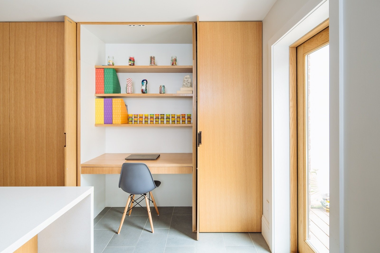 Tucked in a small workspace, just behind the kitchen pantry's pivot pocket doors Tagged: Office, Study, Chair, Storage, Craft Room, Shelves, Porcelain Tile Floor, and Desk.  Brooklyn Brownstone by Sonya Lee Architect llc