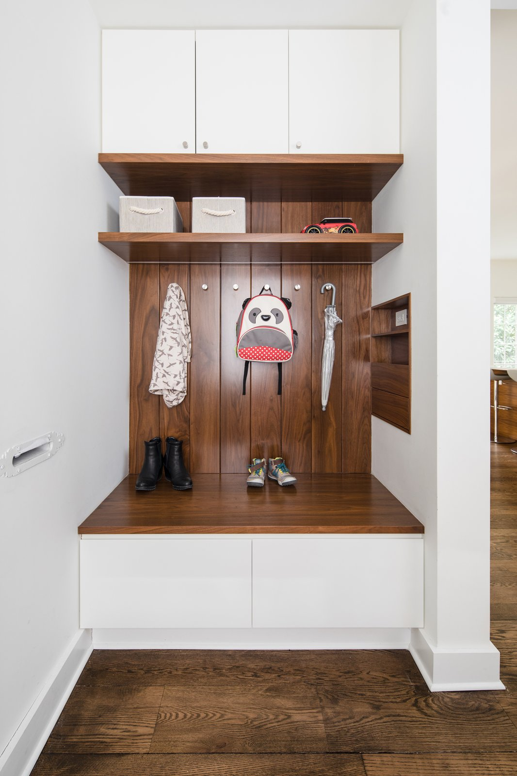 Hallway, Medium Hardwood Floor, and Dark Hardwood Floor Compact mudroom off the front entry offers storage and recessed drawers for mail and all the things you'll likely to lose (including your keys!)   Tennis House by Sonya Lee Architect llc