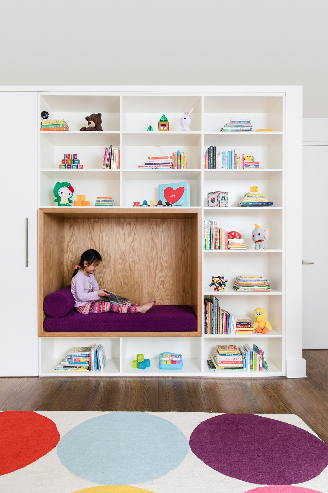 Kids, Shelves, Bookcase, Playroom, Bench, Toddler, Storage, Dark Hardwood, Neutral, Bedroom, and Rug Child's bedroom with custom cabinetry and reading nook  Best Kids Photos from 19 Cozy Nooks That Radiate Charm and Comfort